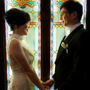 HK wedding couple at China Club, in front of stained glass 1