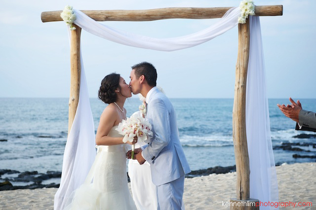 Kona Hawaii US Wedding outdoor bride and groom first kiss beach ocean