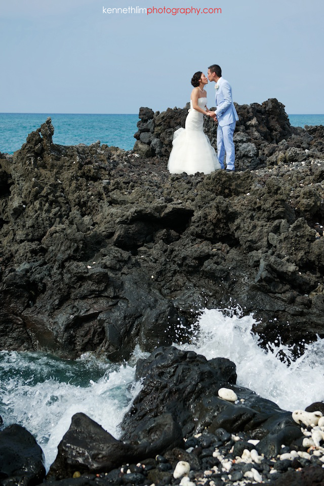 Kona Hawaii US Wedding outdoor bride groom kissing beach ocean rocks waves
