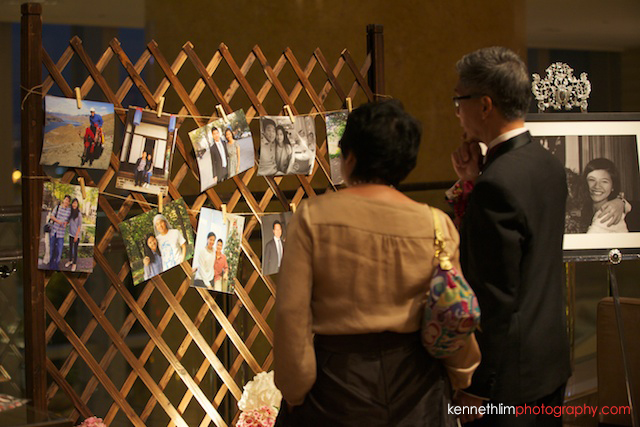 Hong Kong wedding Four Seasons reception guests looking at past photos of new couple