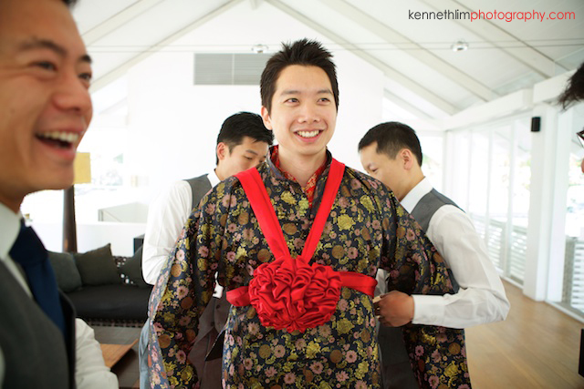 Koh Samui wedding YL Residence morning preparations groom getting ready putting on red ribbon