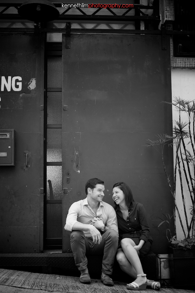 Hong Kong engagement photoshoot outdoors couple sitting down on slanted street black and white