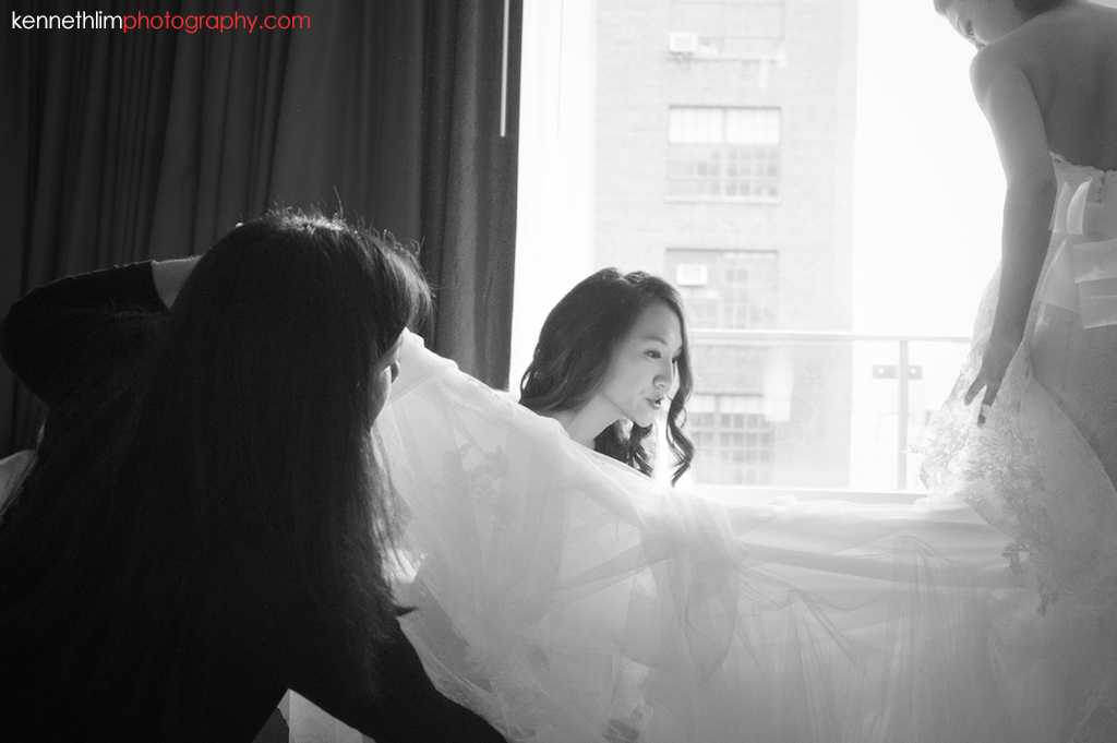 NYC Gansevoort Hotel wedding day photography bridesmaids helping bride with wedding gown