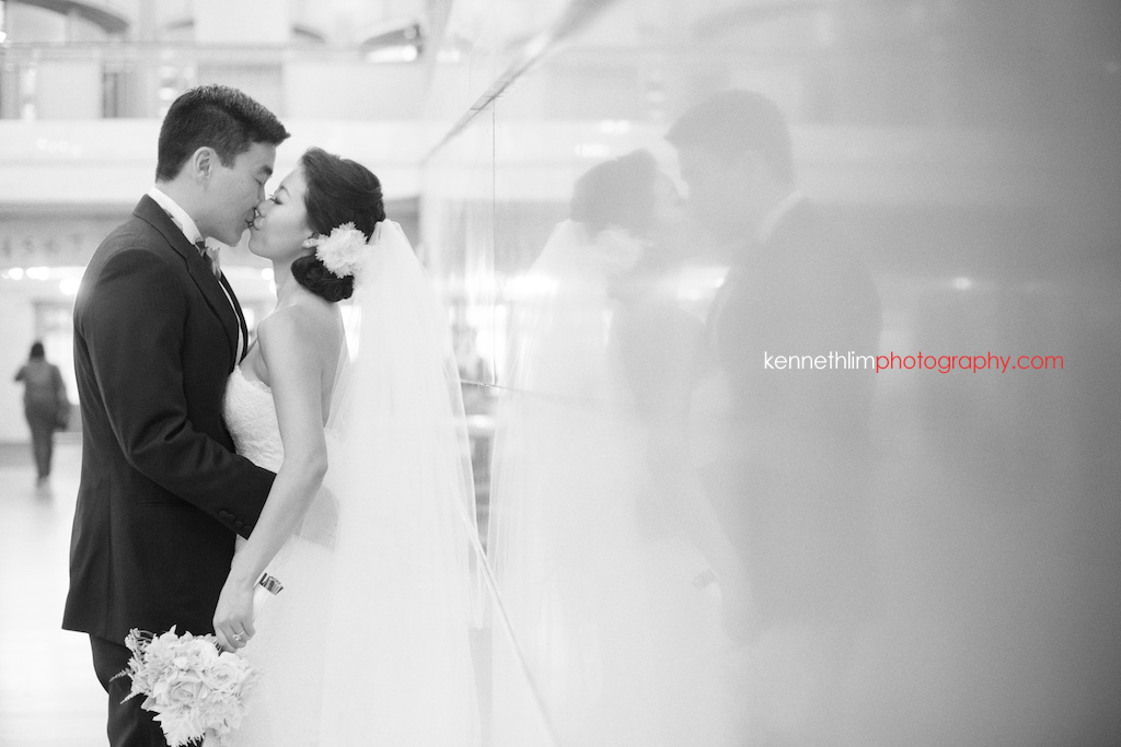 New York City Grand Central Station wedding day photography groom and bride portrait session kissing together against wall