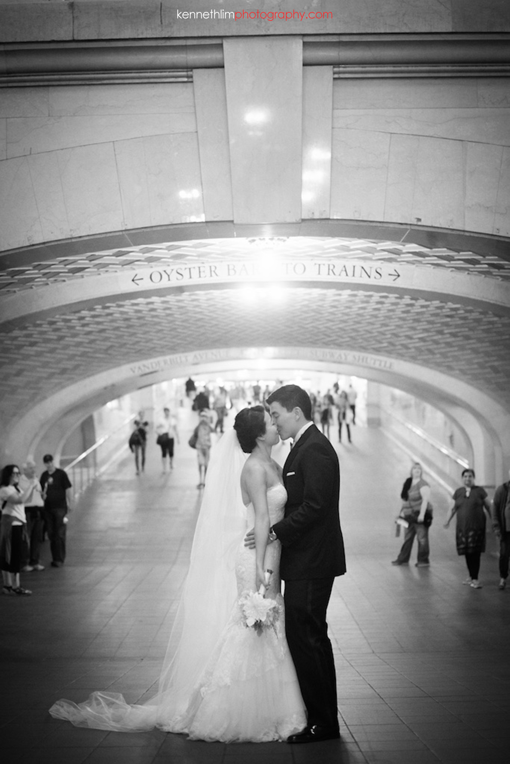 New York City Grand Central Station wedding day photography bride and groom kissing while holding hands