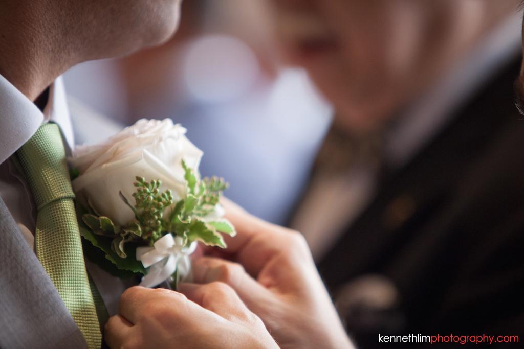 Hong Kong Island Shangri-la Atrium Library wedding day photography groomsmen putting flower on groom morning prep