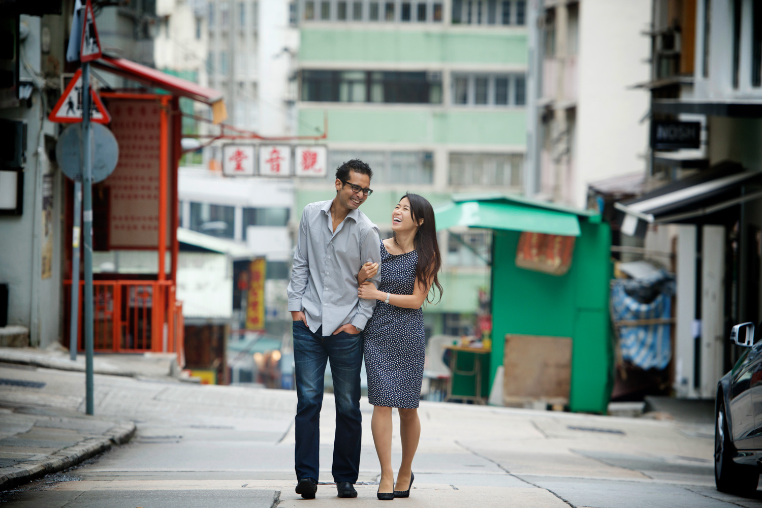 hong-kong-pre-wedding-engagement-photographer-couple-laughing-together-walking-down-street-wan-chai.jpg
