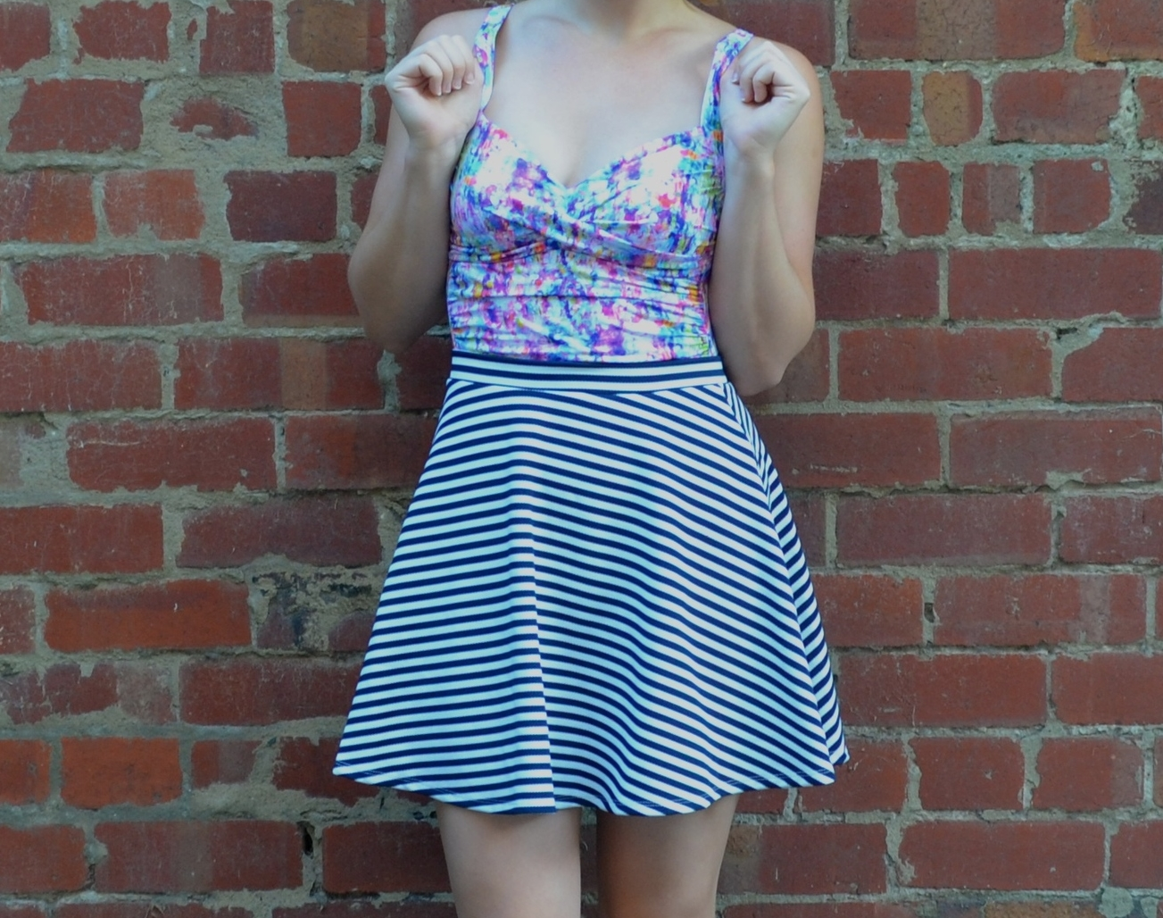 closeup-floral-swimsuit-striped-skirt-brick-wall