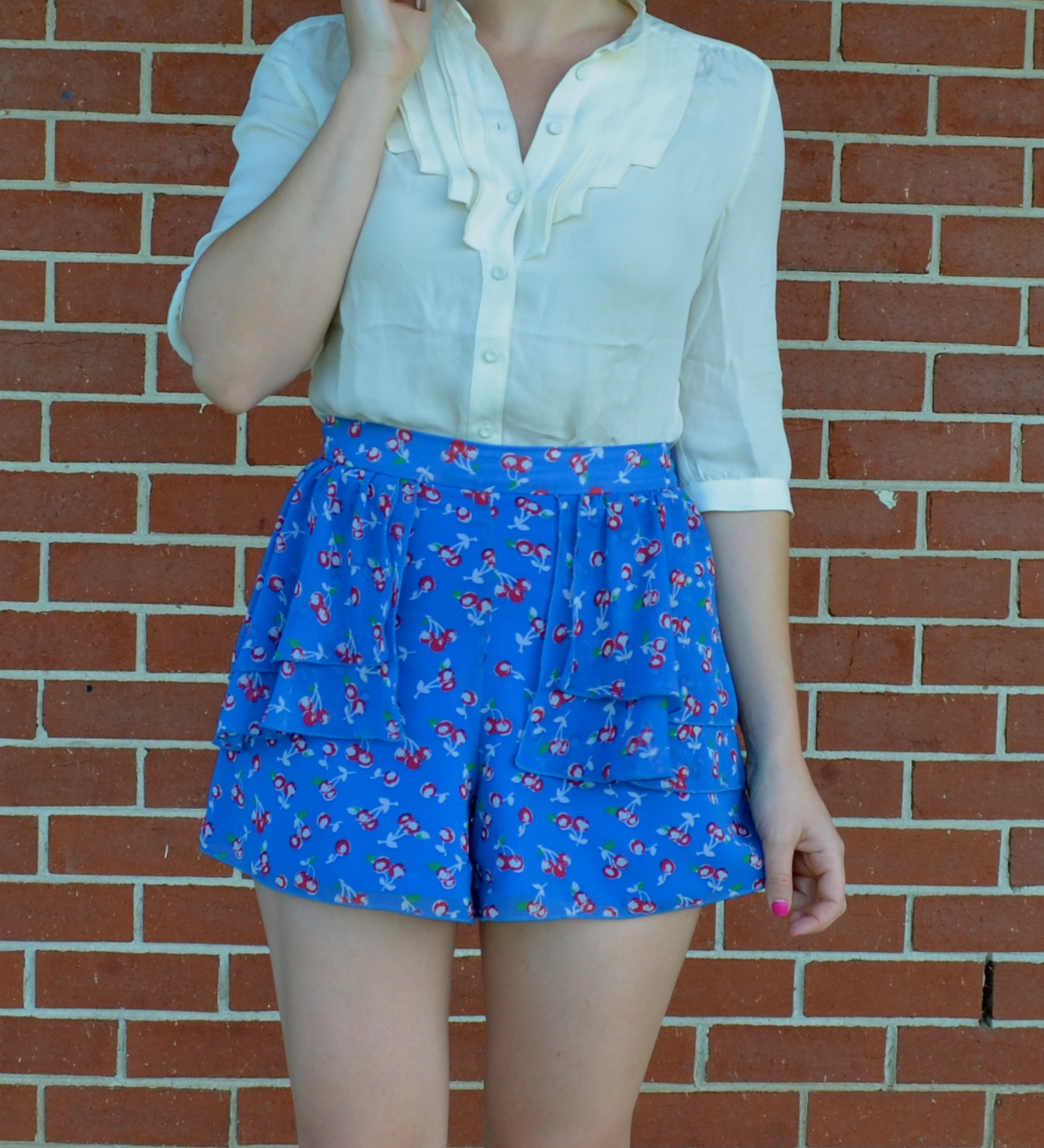 white-blouse-blue-high-waisted-shorts-brick-wall