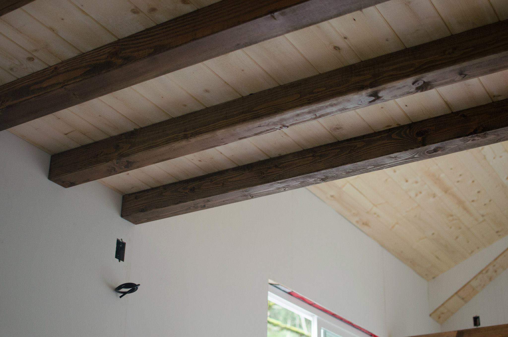 The beams in the living room are custom-milled cedar beams, hand-stained to match the floor.