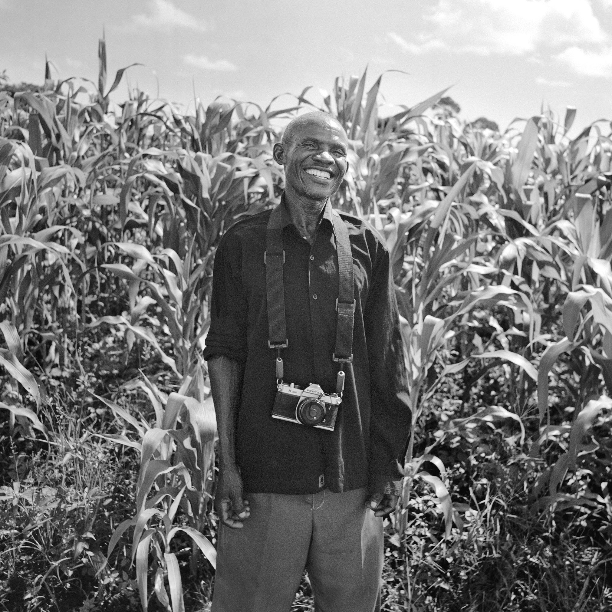 WPC President Waiswa John standing in front of his corn fields.   Here is our WPC President in all his glory and ebullience. Waiswa was a consistent source of positivity and wisdom who consistently brought grace and humor to our collective. He is a strong community leader committed to facilitating agricultural improvement projects in Wanteete;including the construction of a grain grinding mill, and a major reforestation project. He also is the treasurer of the Savings and Credit Cooperative (SACCO) that the WPC started last year from the money they earned through the sale of their photographs.