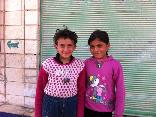 """Little girls from Homs standing outside of their makeshift """"apartment""""."""