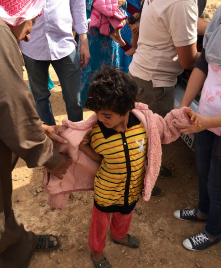 Bedouin kid getting coat.png