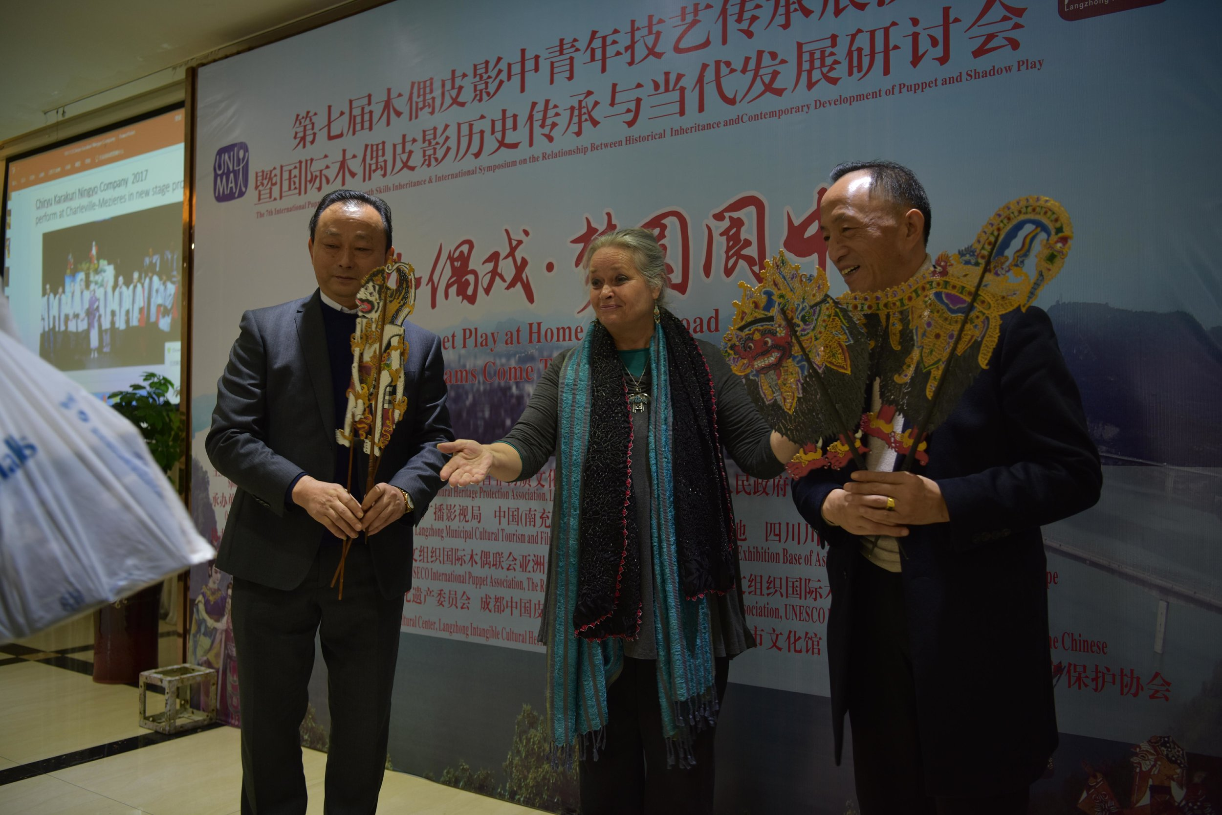 Photo courtesy of UNIMA CHINA. (Left to Right): After introducing the 2020 Bali Congress and World Puppetry Festival, Karen Smith presents two Balinese shadow puppets (Hanuman and Barong) to Wang Biao (Director, Sichuan Wang's Shadow Puppet Troupe) and Wang Fang (Sichuan Wang's Shadow Puppet Troupe).