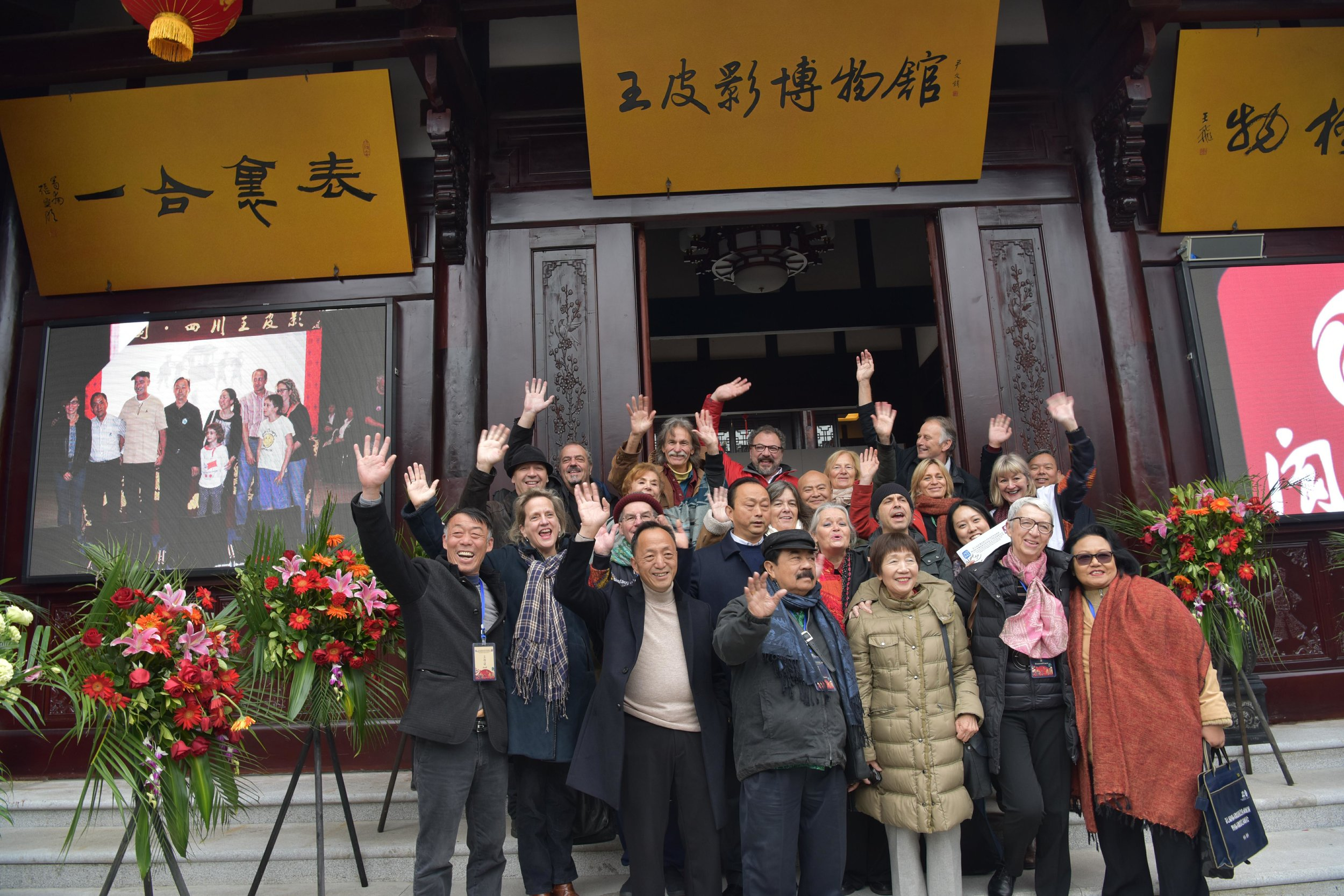 Photo courtesy OF UNIMA China. Outside Sichuan Wang's Shadow Puppet Troupe theatre and museum complex in Langzhong. Back row, L to R: Manuel Dias (puppeteer, Portugal), David Heesen (UNIMA-USA), Tito Lorefice (Argentina, President, UNIMA Professional Training Commission), Joanne Oussoren (UNIMA Netherlands), Frans Hakkemars (UNIMA Netherlands), Chinese gentleman (?)  Upper Middle row, L to R: Nuno do Ó (musician, Portugal), Carol Sterling (UNIMA-USA), Maria José Machado Santos (President, UNIMA Portugal), Chinese gentleman (?), Cariad Astles (British UNIMA, President, UNIMA Research Commission), Julia Davis (UNIMA Australia)  Lower Middle row, L to R: Chinese gentleman (?), Louise Lapointe (Canada, AQM, President, UNIMA International Festivals Commission), Richard Hart (President, UNIMA Australia), Wang Biao (Director, Sichuan Wang's Shadow Puppet Troupe), Karen Smith (UNIMA-USA, Vice President, UNIMA), Tó Zé Bexiga (musician, Portugal), Jinyoung Kim (UNIMA Korea)  Front row, L to R: Wang Fang (Sichuan Wang's Shadow Puppet Troupe), Samodra Sriwidjaja (President, UNIMA Indonesia), Yasuko Senda (UNIMA Japan-Nihon UNIMA), Lucile Bodson (Treasurer, UNIMA), Yulita Samodra (UNIMA Indonesia).