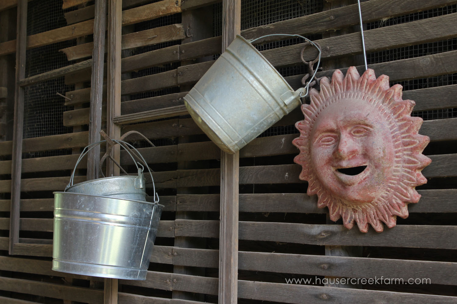 Metal buckets and sunshine sculpture hanging on wooden slatted wall
