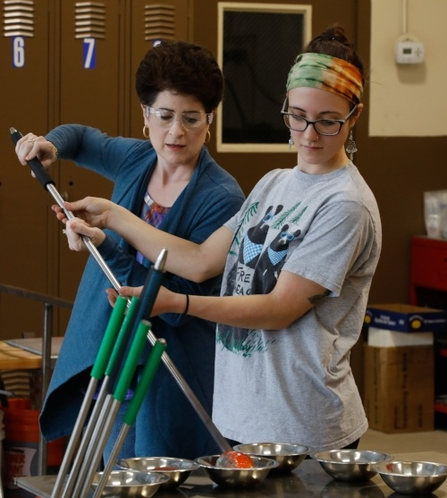 Instructor, Hannah Muller, helping first time student add color to her glass