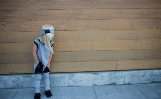 Harlan wearing the unisex romper and faux leather headband.