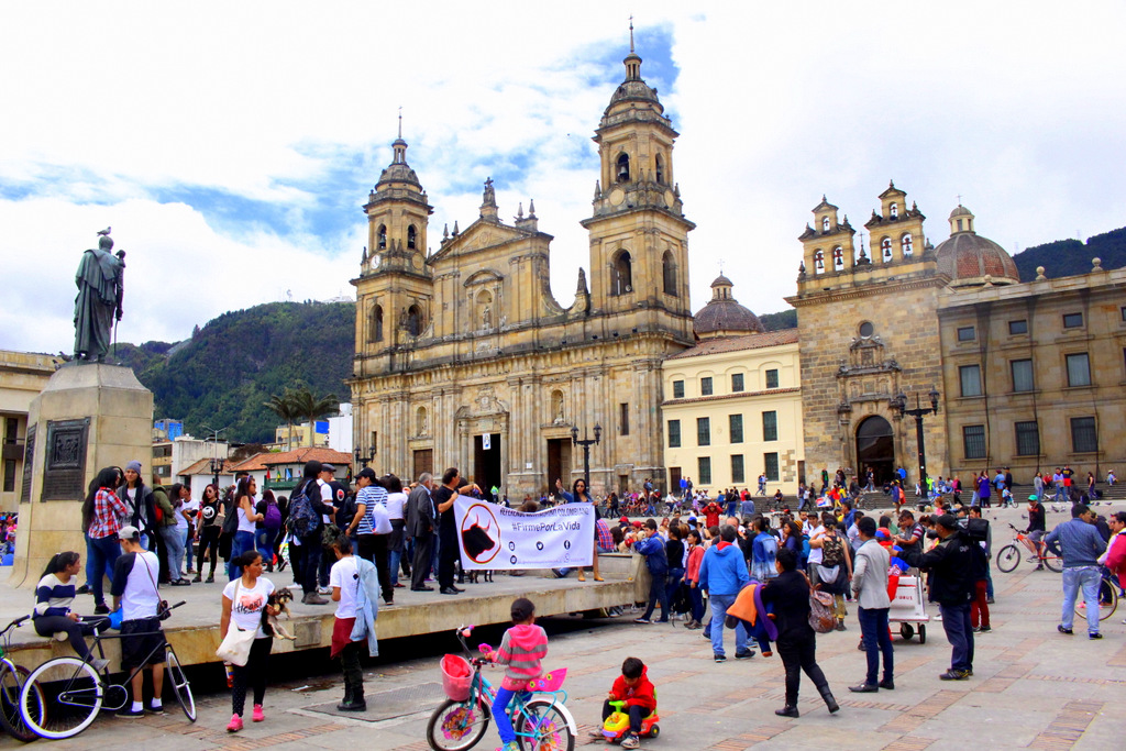 Plaza Bolivar is the heart of  Bogotá with many historic buildings. The 19th century Catedral Primada sits as a backdrop while locals rally in the square.