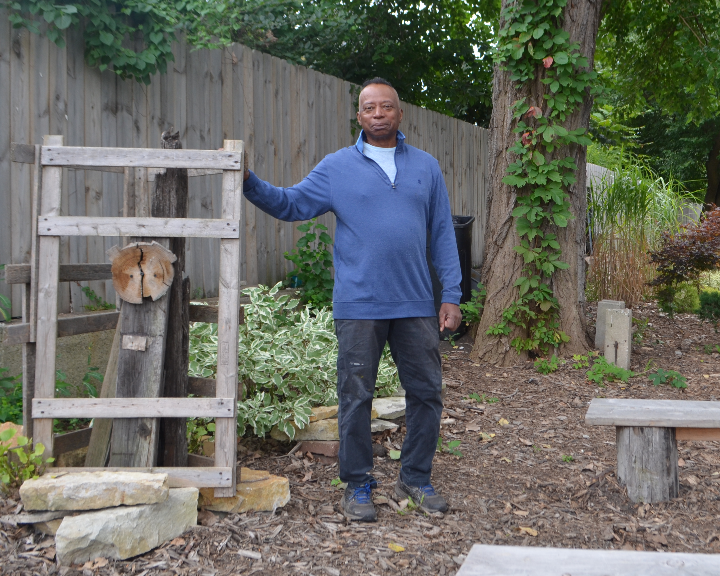 William Hill at his Dorchester Botanical Garden next to sculpture and benches he created