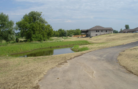 Road with small pond at Tuscan Ridge Condominiums in Deforest, WI