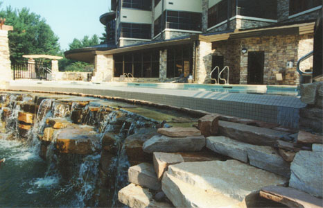 outdoor pool area with small rock waterfall at Sundara Inn & Spa in Lake Delton, WI