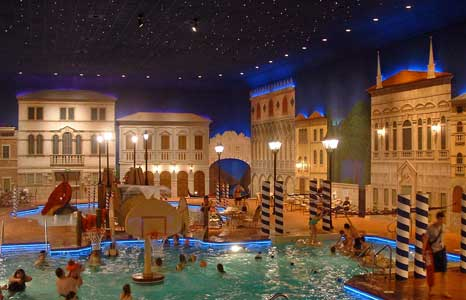 A busy Indoor pool with a nighttime city street theme at the Holiday Inn in Maple Grove , MN