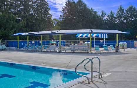 Outdoor lap pool with seating area at the Hill Farm Swim club in Madison, WI