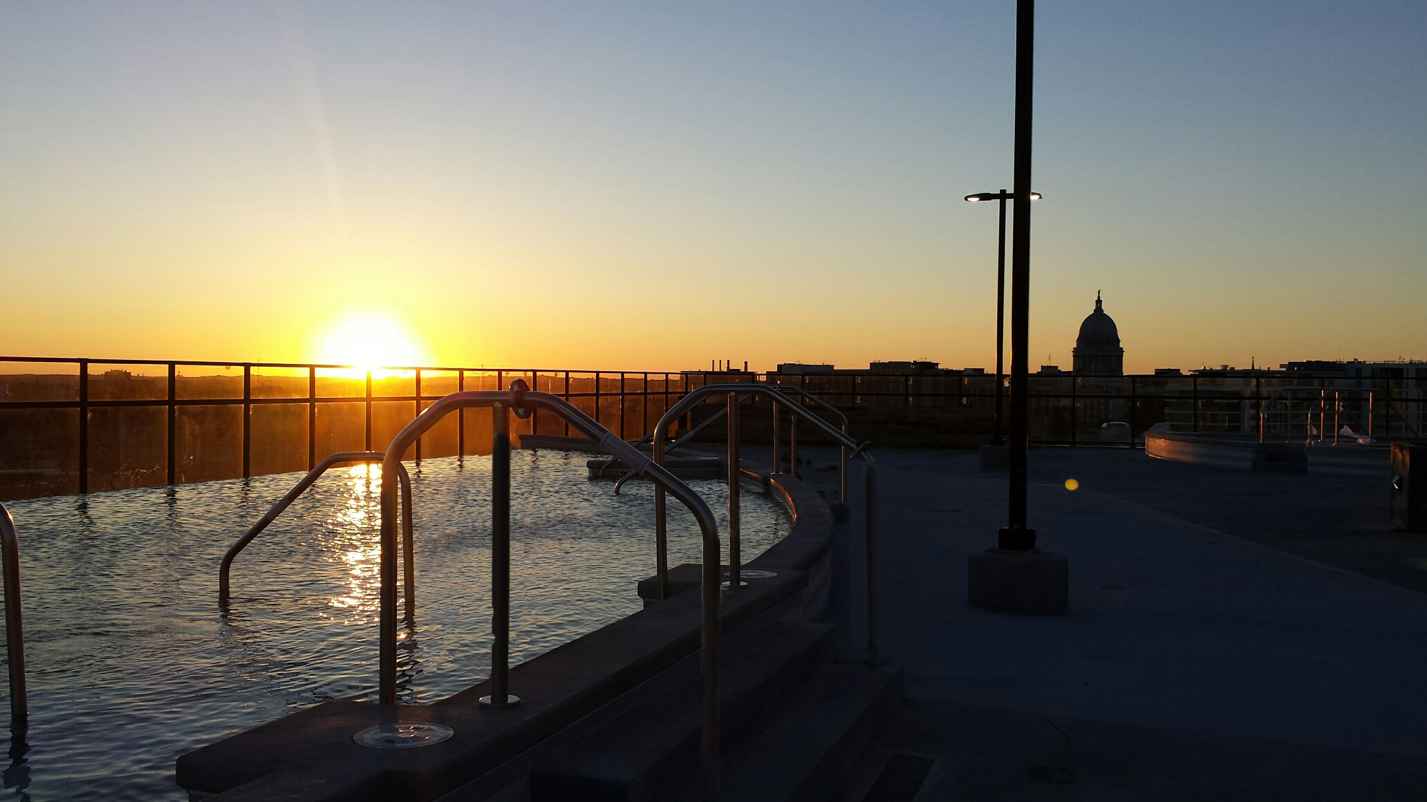 Sunset view of the outdoor rooftop pool at The HUB in Madison, WI