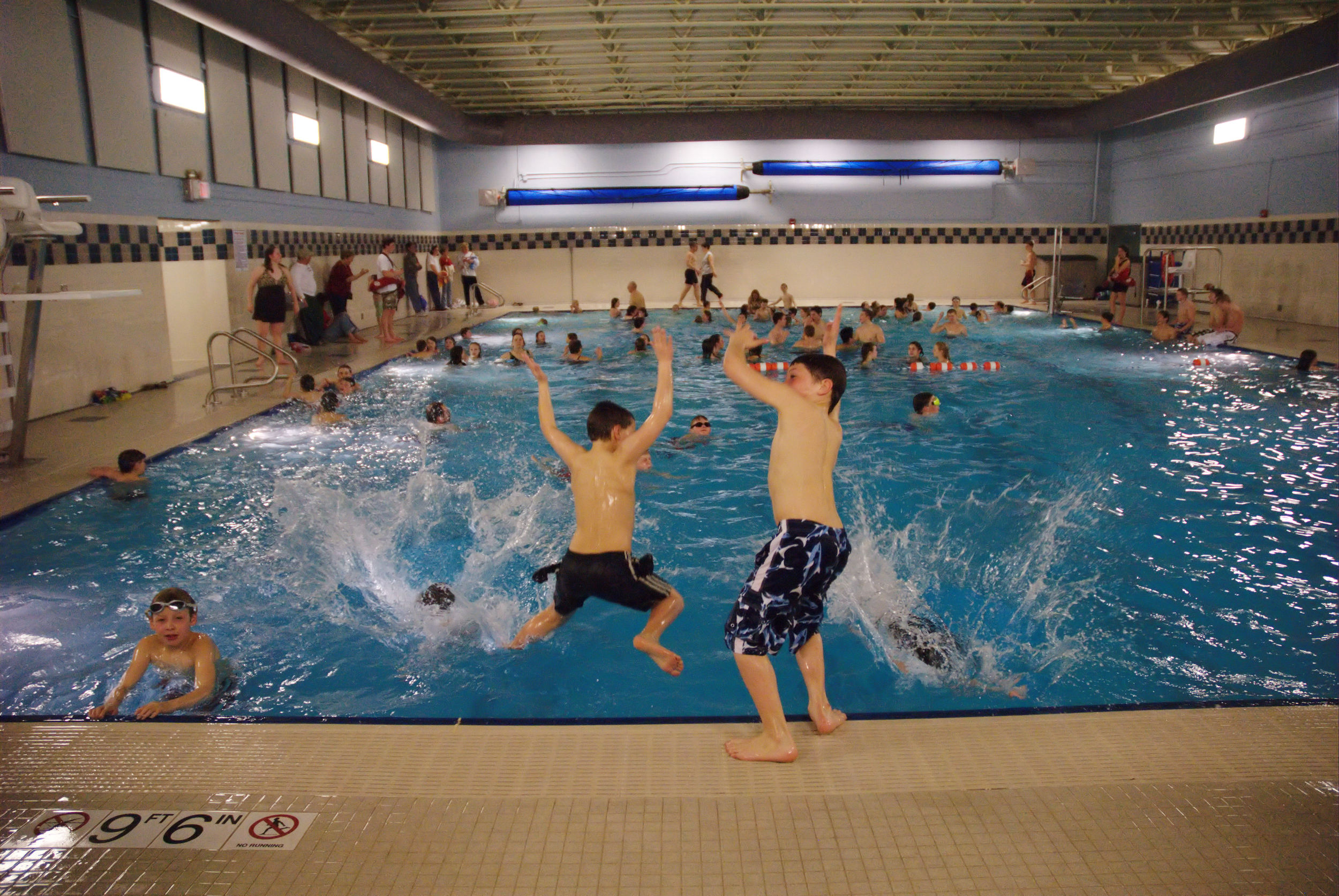 Kids jumping into a busy pool at Poynette High School in Poynette, WI