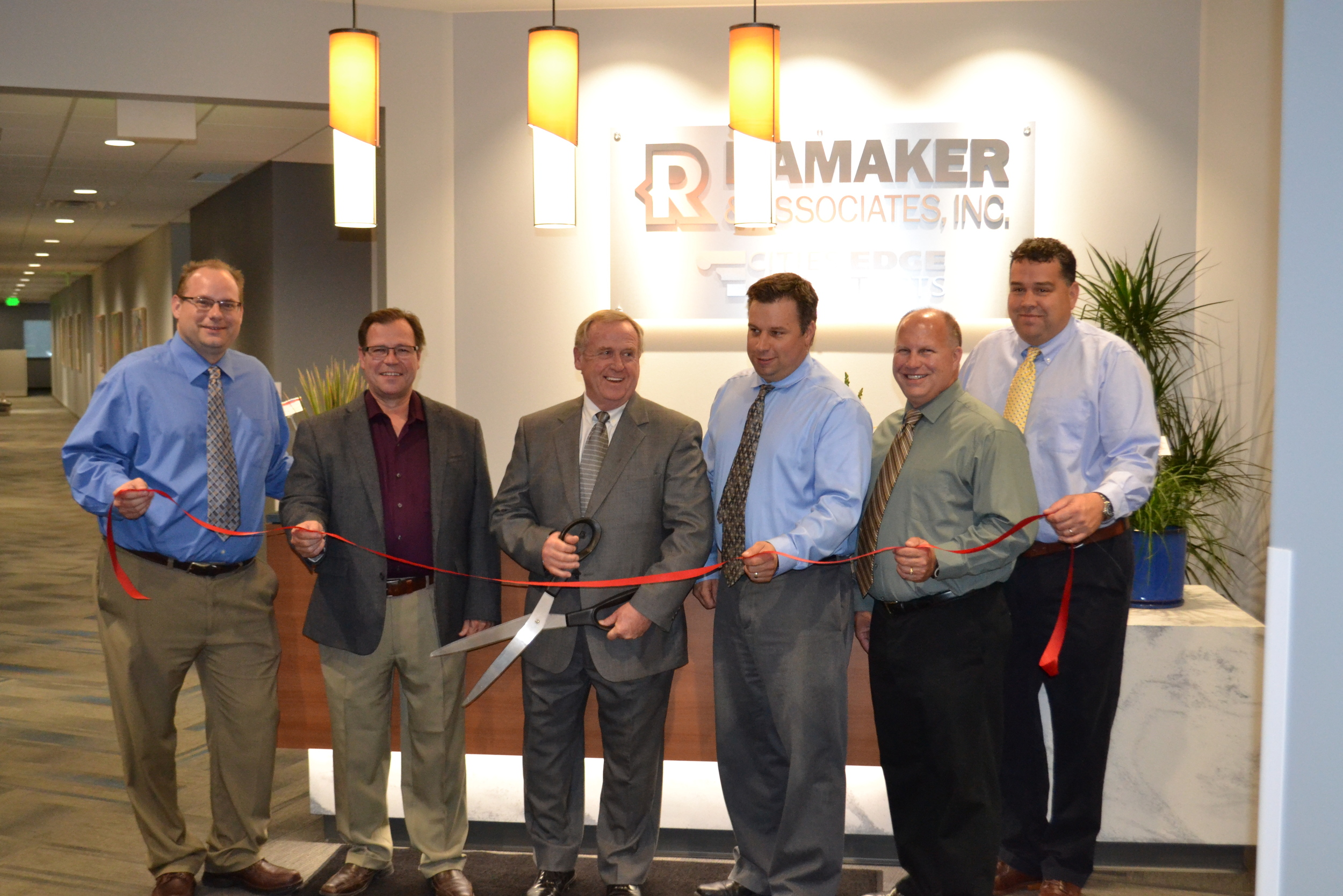 Ribbon cutting inside by the front desk at the Sauk City office