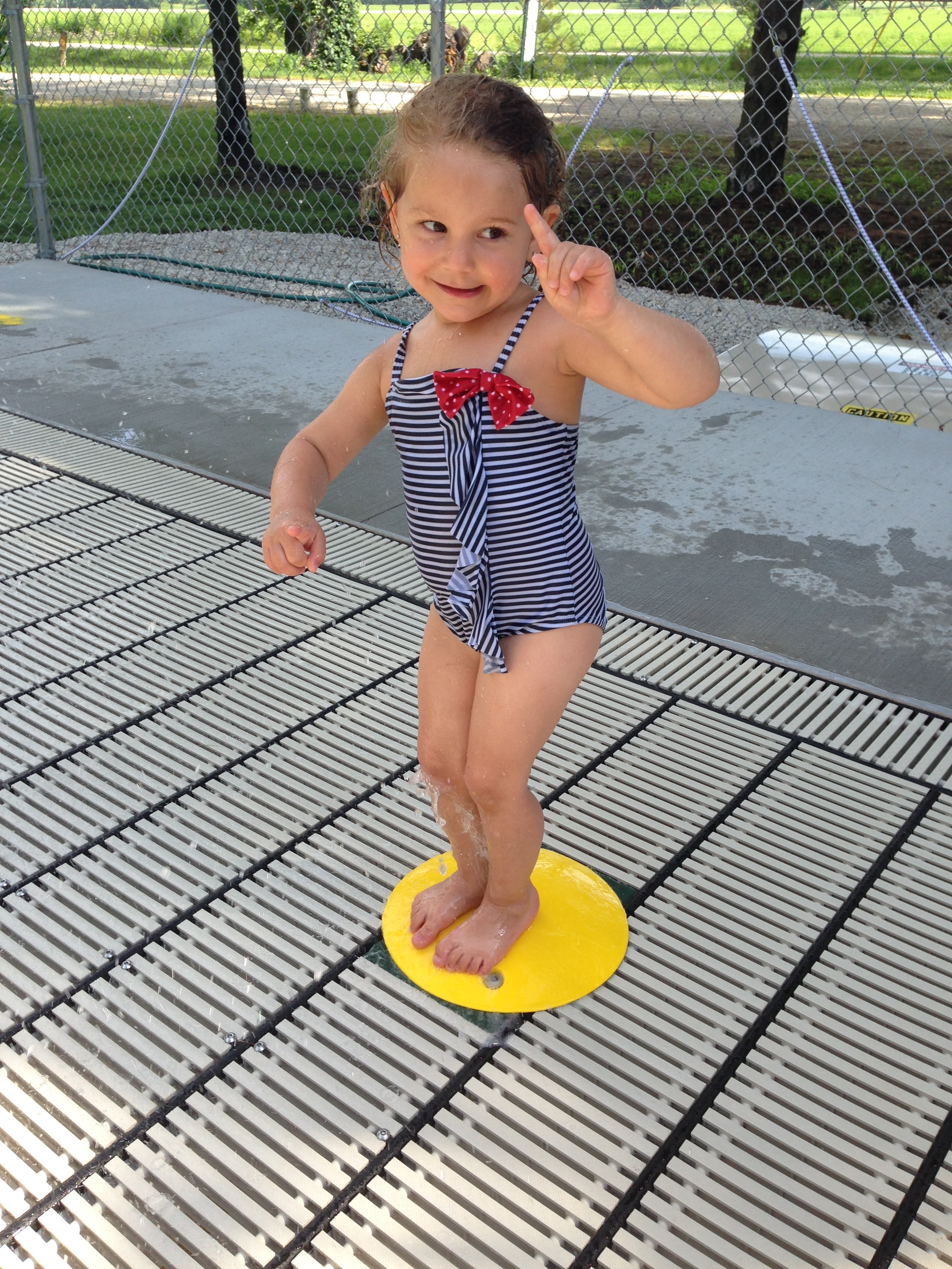 Girl play on  water spray deck at Geneseo Campground in IL