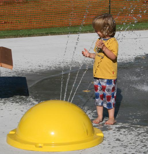 A kid playing at the outdoor splash pad area at El Dorado Sprayground in KS