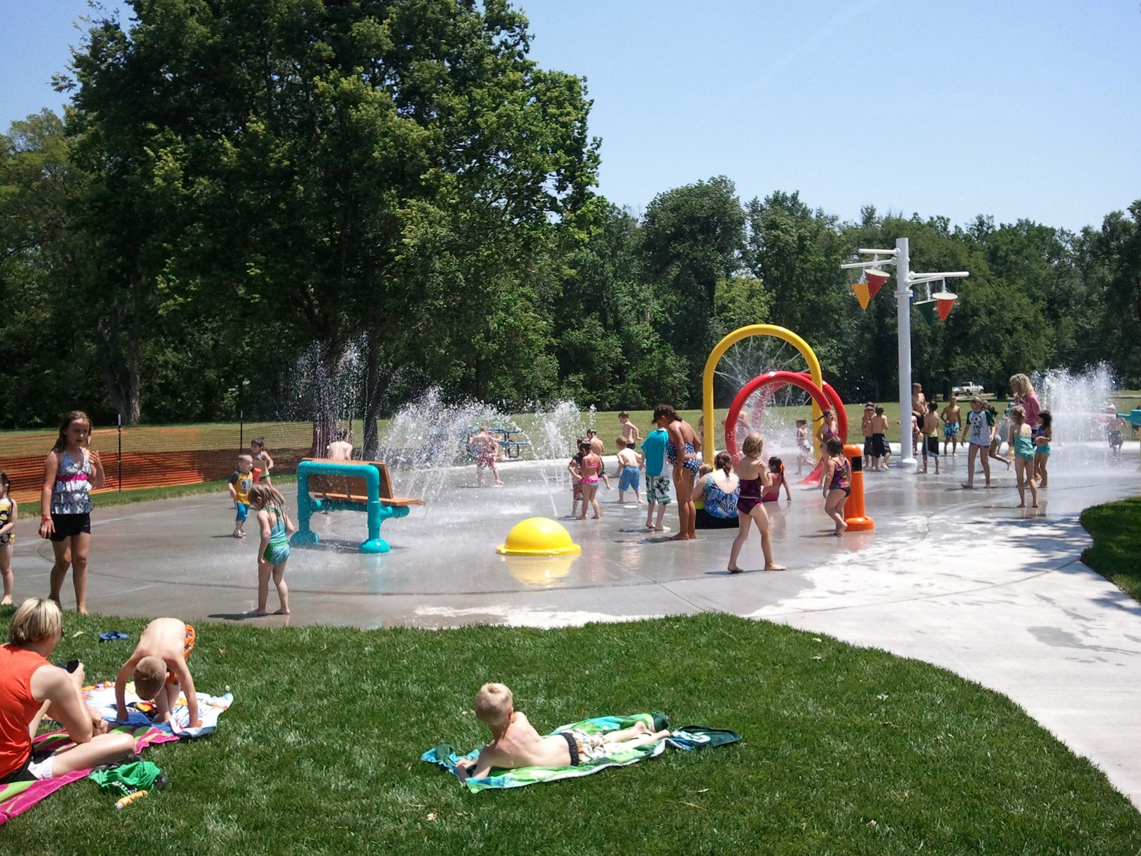Kids playing at the outdoor splash pad area at El Dorado Sprayground in KS