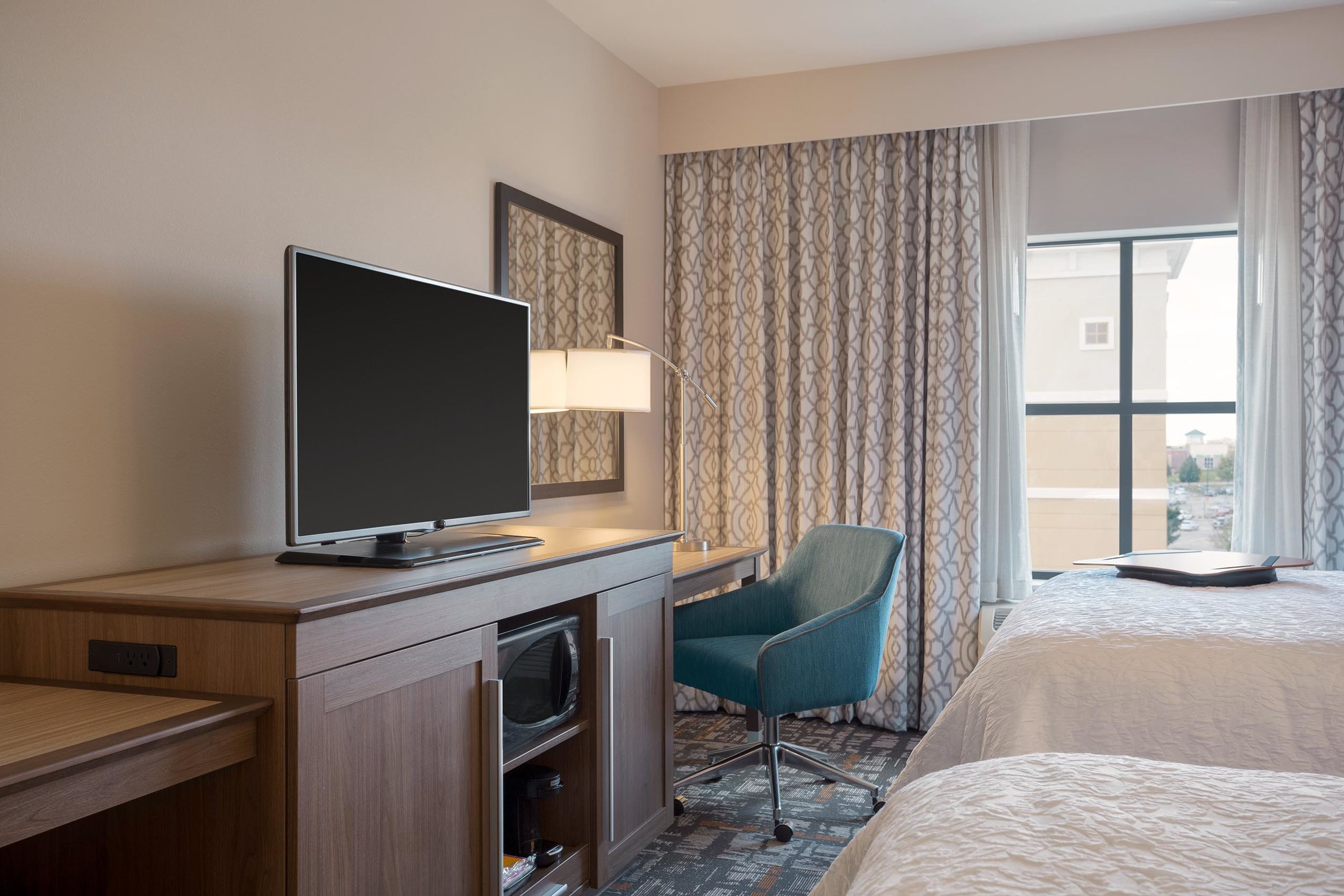 TV and desk area in a bedroom in the Hampton Inn & Suites in West Des Moines, IA