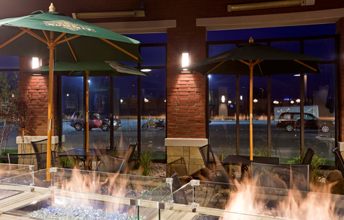 Inside seating area by a fireplace at Green Mill in Willmar, MN