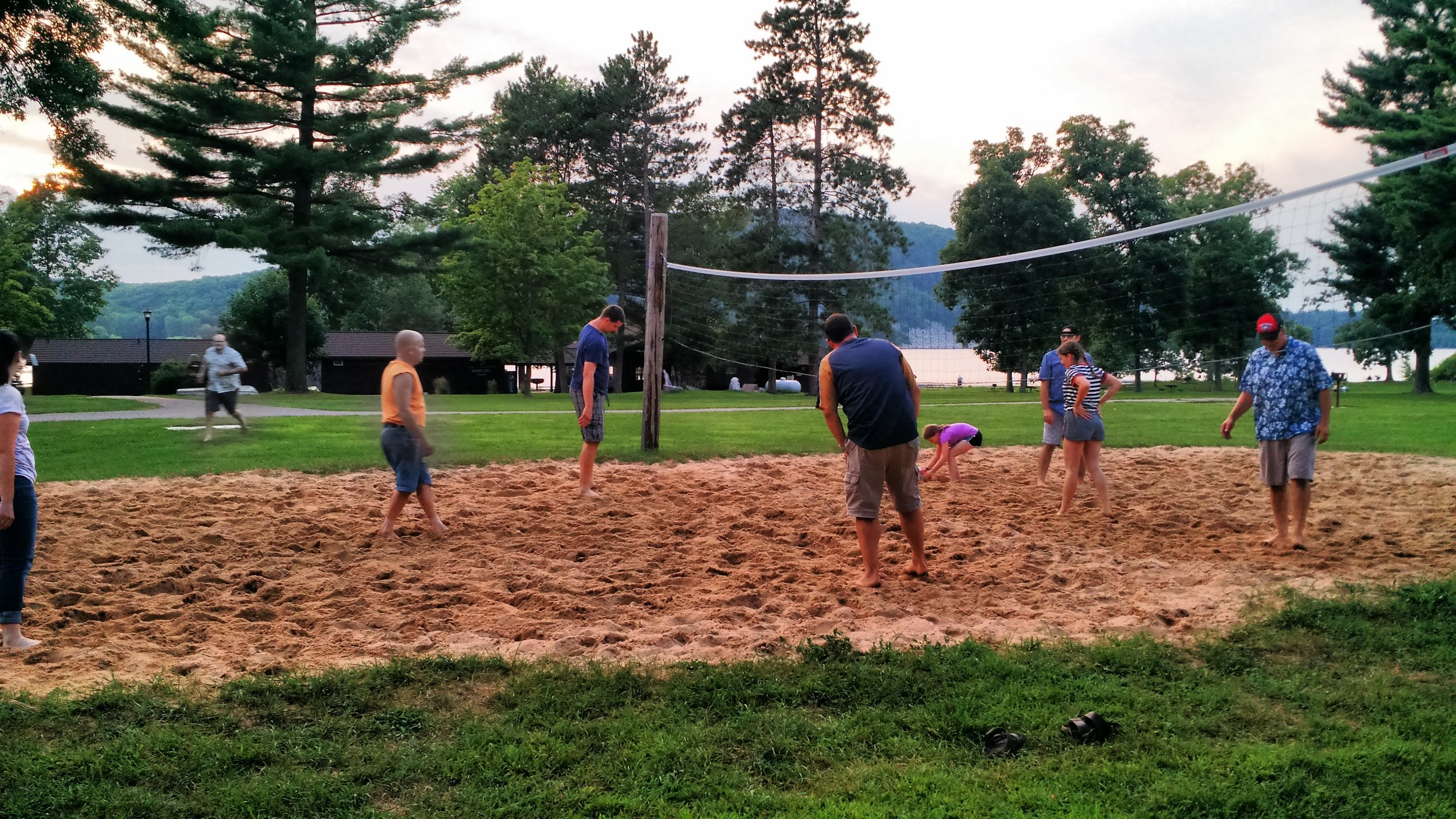 Employees playing volleyball outside on a sand court
