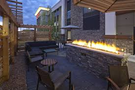 Outdoor seating area with a fireplace at the Hampton Inn Hometown in Spicer, MN