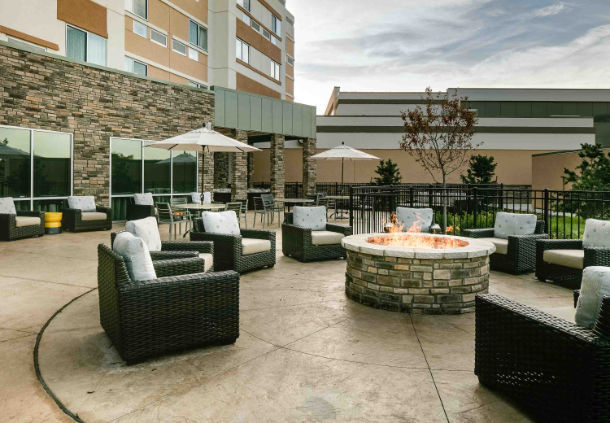 Outdoor seating area with a fireplace at the Courtyard Hotel in Bellevule NB