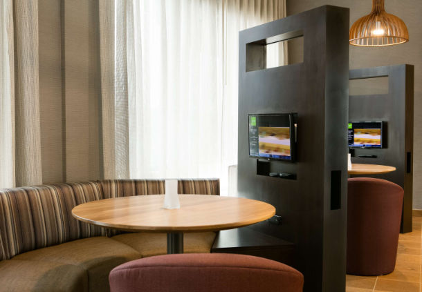 Smaller personal seating area with TVs the Courtyard Hotel in Bellevule NB
