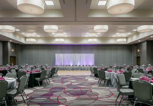 Banquet room with chairs, table, and stage in the Courtyard Hotel in Bellevule NB