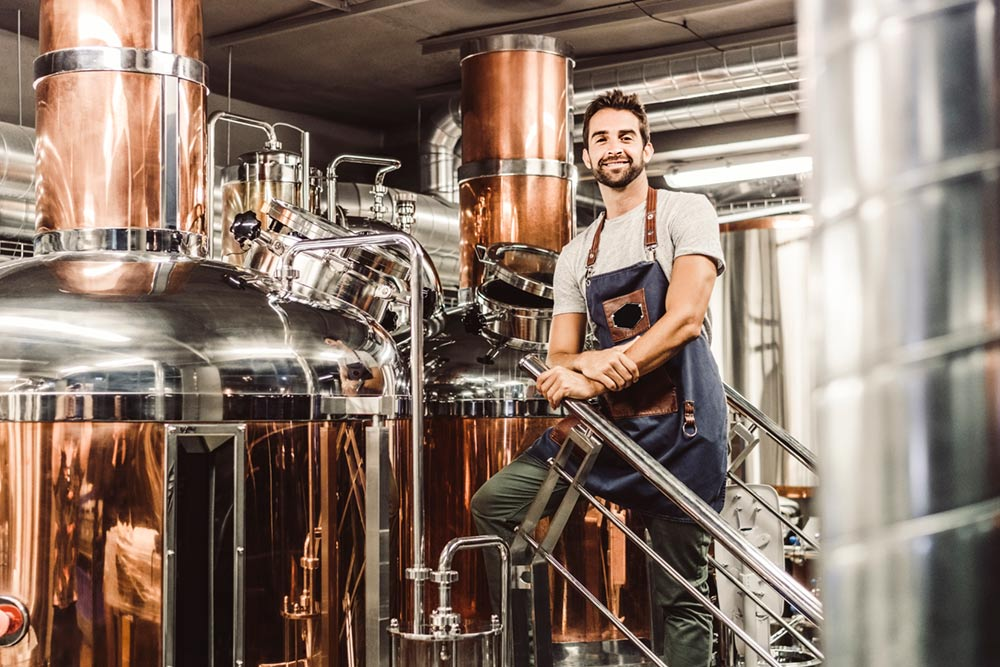 Brewmaster next to clean brewery tanks