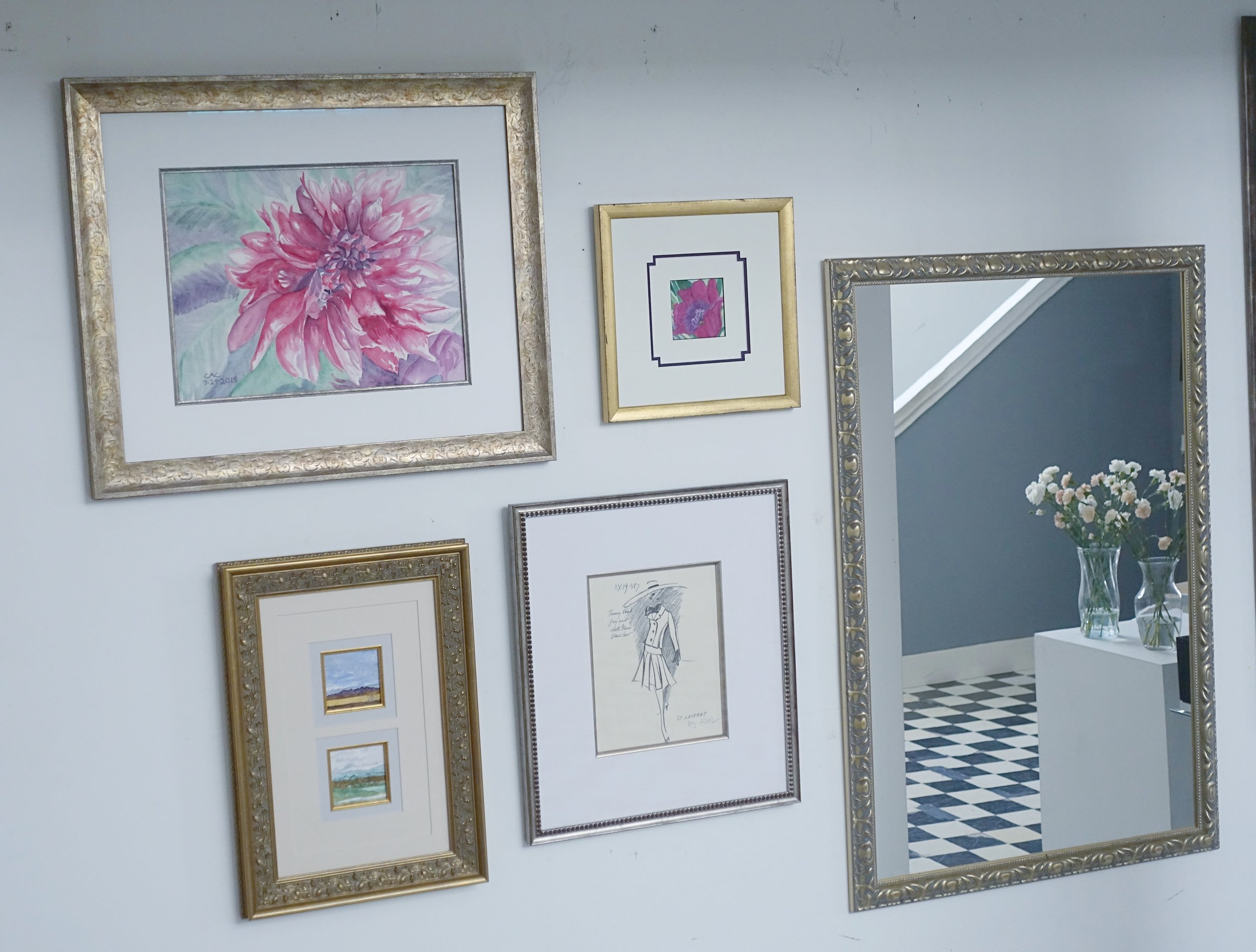 Gallery wall at the shop. Each frame design is different, but the arrangement of color and mood build balance and cohesion. The placement of the mirror broadens the space.   Watercolors by Carol Ann Conners; Fashion illustration by Ruth