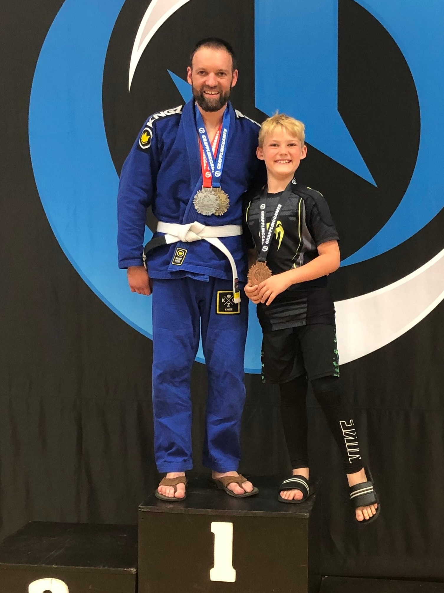 Father (Ron Wiza) and son (Cooper Wiza) both competed at the Grappling Games tournament held on June 22, 2019 in Oak Lawn, IL and each came home with medals. Ron Wiza received a silver medal after competing against someone more than half his age in the adult division.