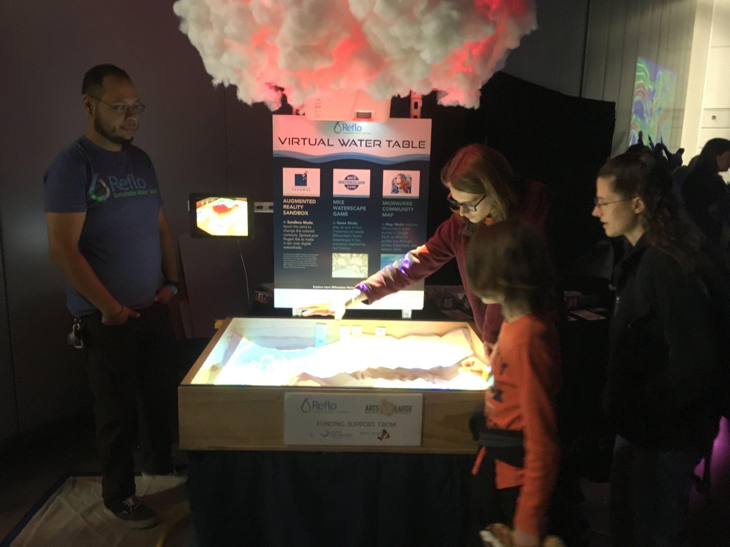 Reflo's Jose Basaldua watches as a family explores the Augmented Reality Sandbox.