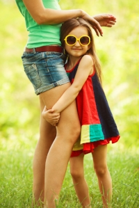 Young girl clinging to mothers leg, slow to warm up or cautious child