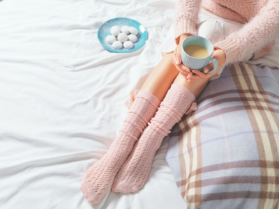 Woman in pink socks and sweater relaxing on bed with tea.