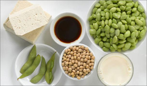 Table with multiple different soy products: tofu, edamame, soymilk, soy sauce, dried soybeans and fresh soybeans