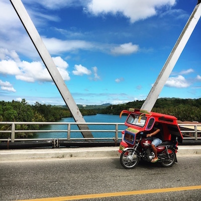 A taxi tryke swooping past above the Loboc river.