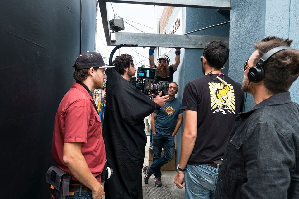 DP Matt Mayotte holding the camera, with Gaffer Cyrus leaning on the wall, and Boom operator David behind him.